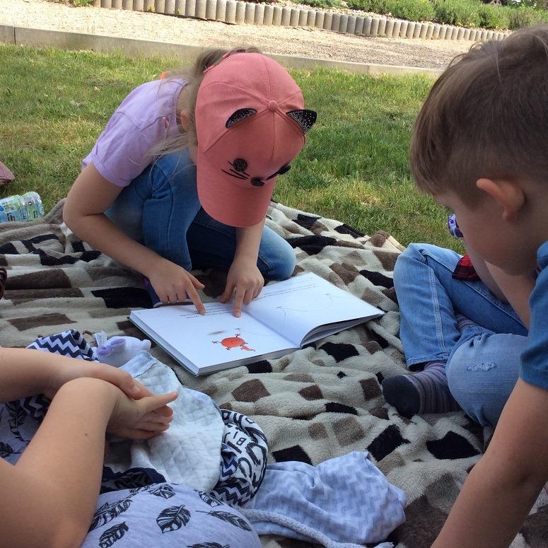 dzieci czytają siedząc na trawniku